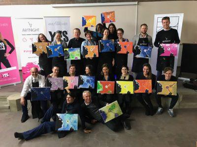 Eines von den Projekten der Deutschen Stiftung Eierstockkrebs: Die Teilnehmer des Projekts Charity ArtNight halten allesamt ihre malerischen Werke in der Hand und präsentieren sie lachend dem Betrachter. Im Hintergrund stehen Aufsteller, die Plakate der ArtNight und YESweCancer - Initiative halten.